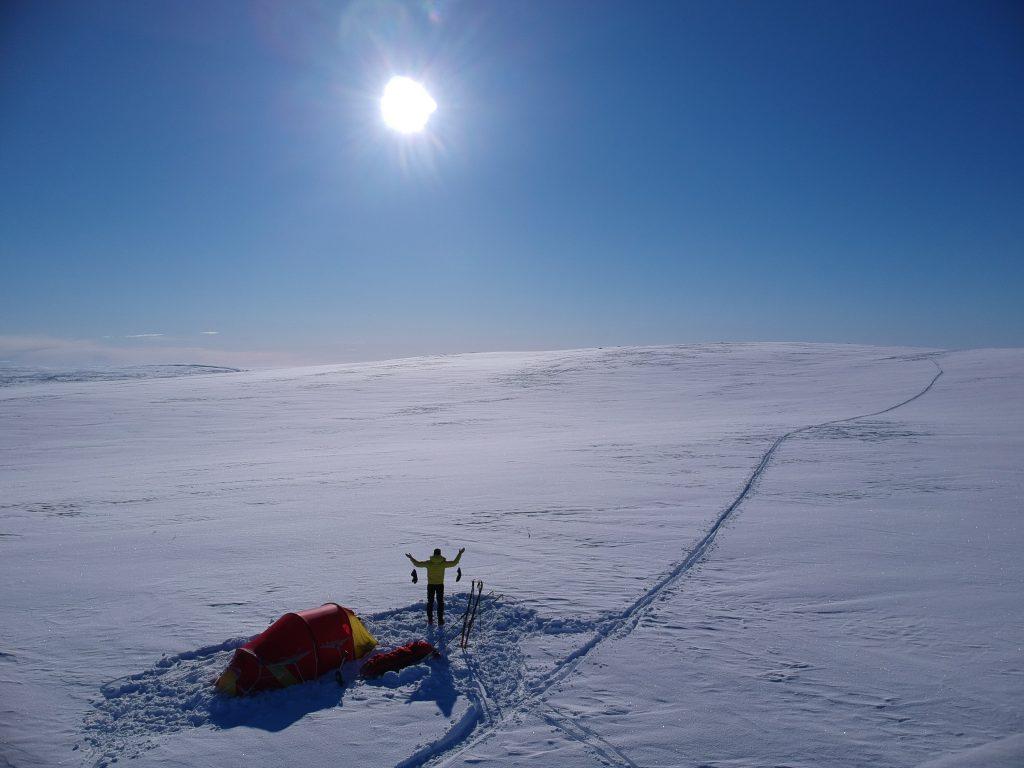 Person står utenfor teltet og ser utover store, snødekte vidder og blå himmel