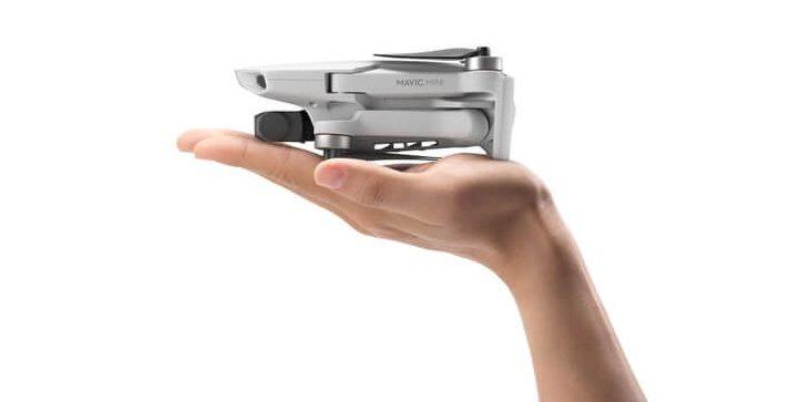 DJI Mavi mini-drone ligger i en håndflate. Dronens propeller er sammenfoldet.