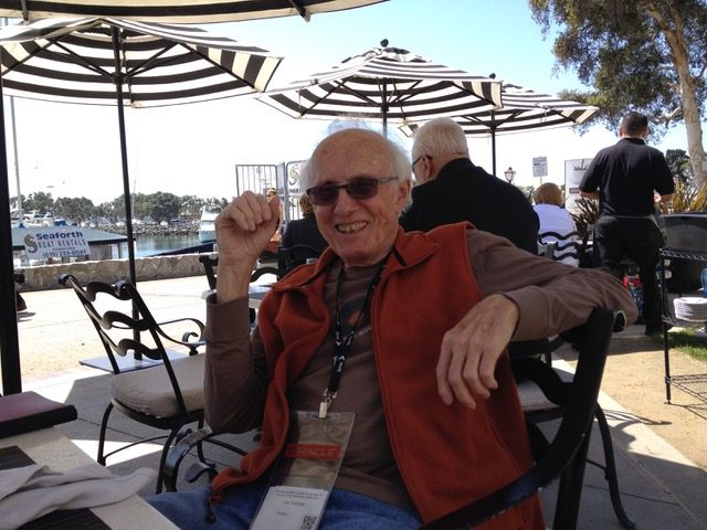 Jim Thatcher sitter ved et bord på en utekafé under parasoller i solskinn. Han har solbriller på og smiler.