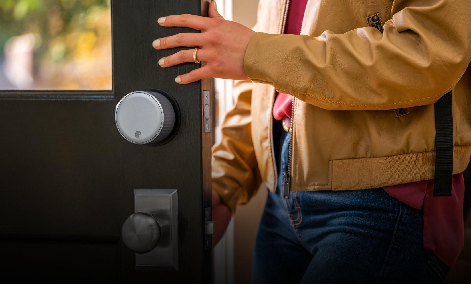 En rund, sølvfarget Wi-Fi Smart Lock er festet over håndtaket på en åpen dør. En kvinne er på vei ut døra.